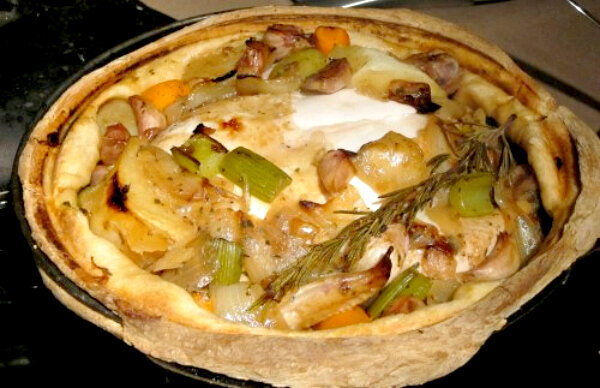 whole braised chicken with vegetables under a flaky crust.