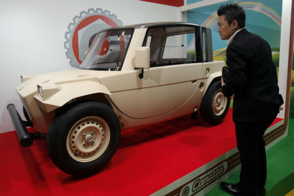 a visitor looks at a concept of the camatte electric car displayed by toyota motor co for children to drive during the international tokyo toy show in