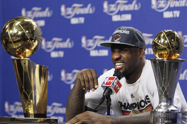 The Miami Heats LeBron James Sits Between Larry OBrien NBA Championship Trophy Left And Most Valuable Player After Game 5 Of