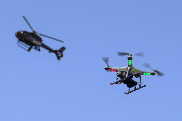 A Police Helicopter Flies Past UAV Drone Which Was Flying Over Post March Street Celebration In West Baltimore Maryland