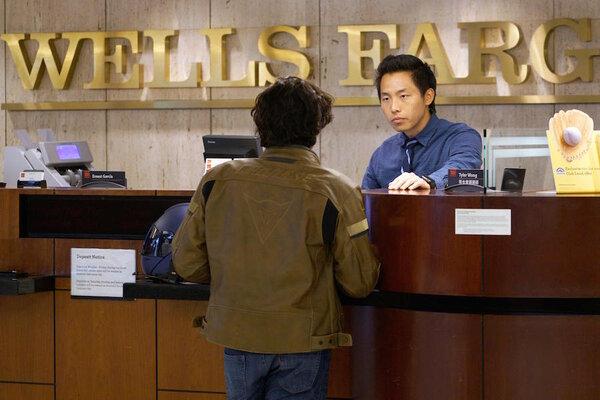 Bank Teller Tyler Wong Talks To A Customer At The Wells Fargo In Denver