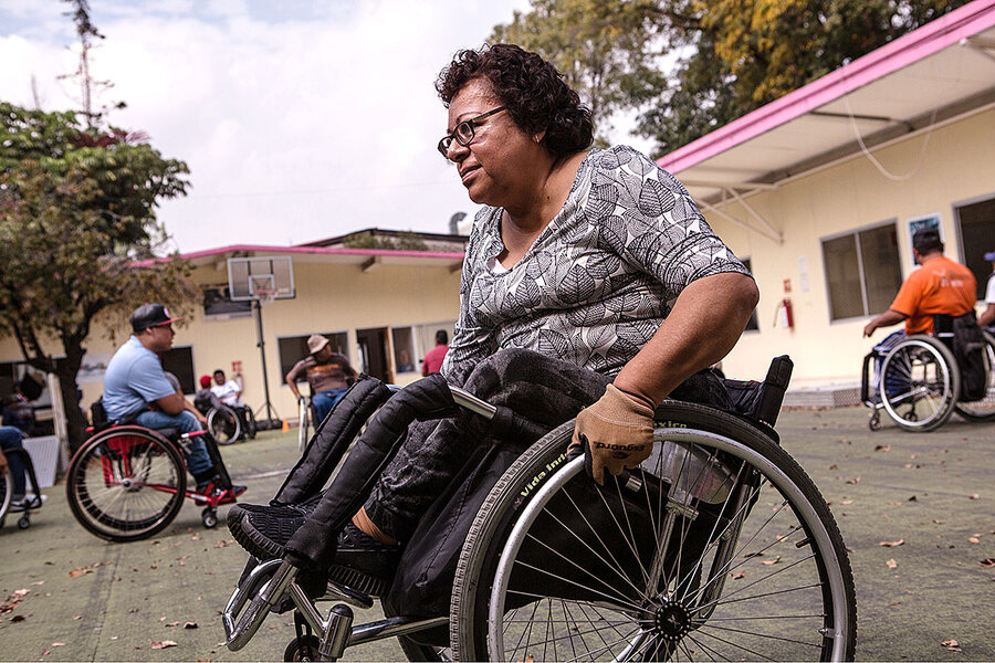 Woman in wheelchair in outdoor courtyard, with other wheelchair users in background.