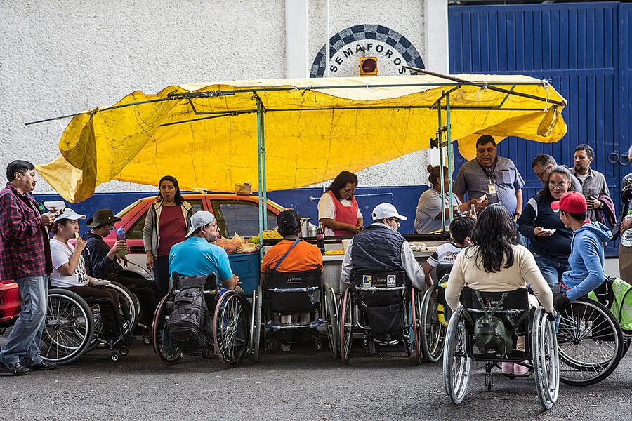 Group of wheelchair users gather under a yellow tarp outside while eating.