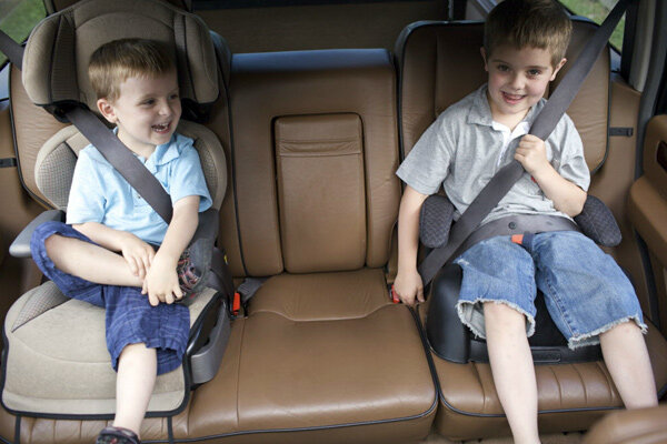 and dennis austin sit in their car booster seats waiting to go on a quick car trip with their parents